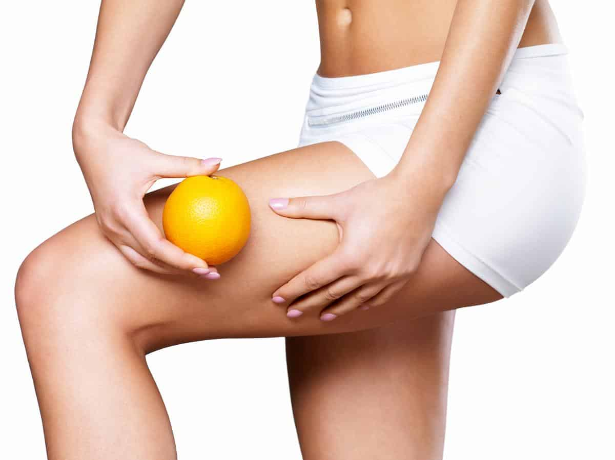 Female squeezes cellulite skin on her legs – close-up shot on white background